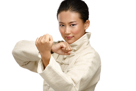 Beautiful asian woman make kung fu gesture  on white photo