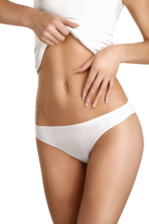 vientre femenino: primer plano de una mujer joven que muestra el vientre muy plano en blanco Foto de archivo