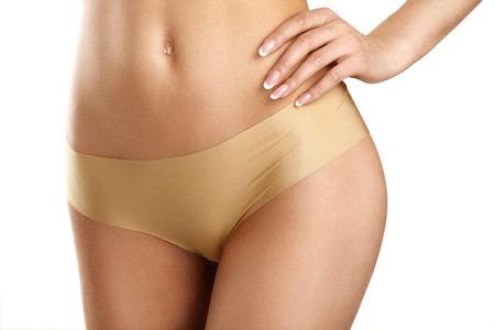 primer plano de una mujer joven que muestra el vientre muy plano en blanco Foto de archivo