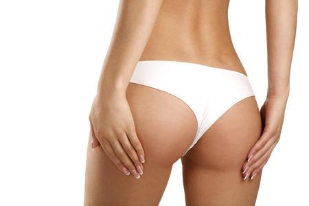 nalga: Primer plano de una mujer hermosa que muestra las nalgas perfectas en blanco