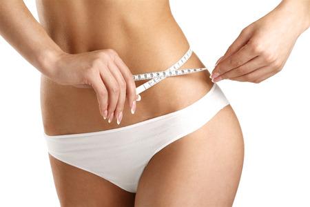 Primer plano de una mujer que mide sus caderas en blanco