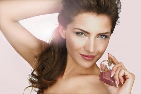 Primer plano de un hermoso perfume efecto de luz de fondo mujer de la aplicación