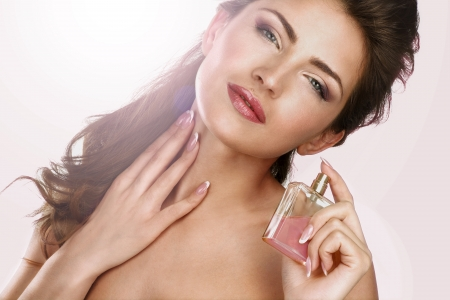Closeup of a beautiful woman applying perfume backlight effect