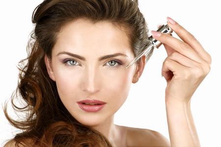 Primer plano de una hermosa mujer de aplicar un tratamiento de belleza en blanco Foto de archivo