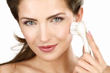 Closeup of a beautiful woman applying a beauty treatment on white photo