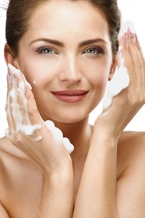 soap foam: Beautiful woman cleaning her face with a foam treatment on white