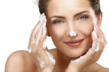 Hermosa mujer de limpieza de su cara con un tratamiento de espuma sobre blanco