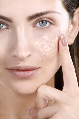 Beautiful woman applying scrub treatment on face closeup photo
