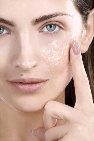 Beautiful woman applying scrub treatment on face closeup