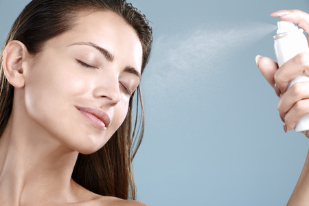 Beautiful woman applying spray  water treatment on face on blue wall