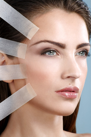 Beautiful woman applying tape lifting treatment on face on blue wall Banque d'images