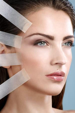 Beautiful woman applying tape lifting treatment on face on blue wall Standard-Bild