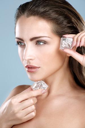 cubetti di ghiaccio: Bella donna che applica un trattamento cubo di ghiaccio sulla parete blu