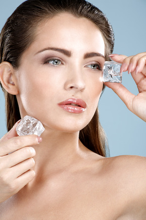 Beautiful woman applying ice cube treatment on blue wall