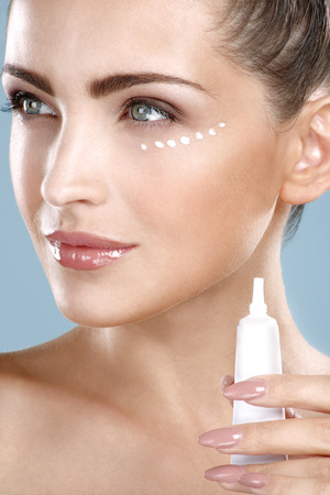 Beautiful woman applying cream treatment on her perfect face on blue photo