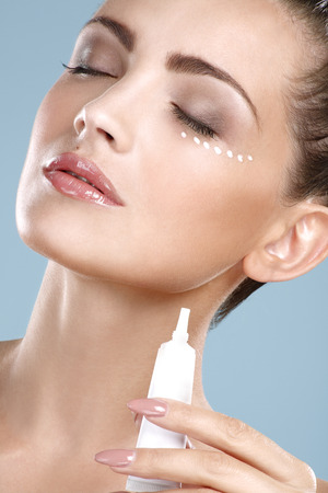 Beautiful woman applying cream treatment on her perfect face on blue