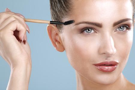 Closeup beautiful woman with eyebrow brush tool on blue 写真素材