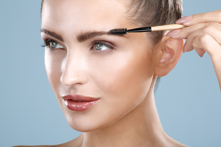 Closeup beautiful woman with eyebrow brush tool on blue Фото со стока