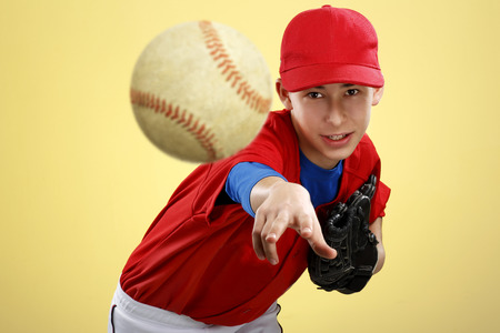 portrait of a beautiful teen baseball player in red and white uniform on colorful background Stock Photo