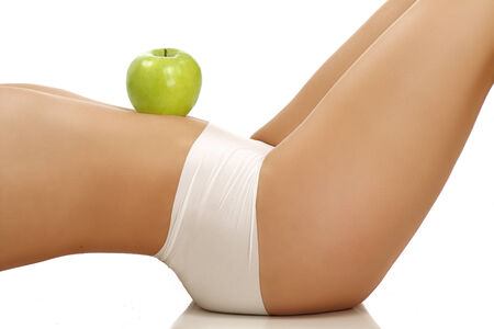 Closeup of a perfect girl showing a fruit on her body on white photo