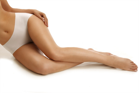 fine legs: Closeup of a  girl lying on the floor showing beautiful legs on white