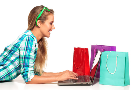 Young Woman Sitting at the desk  shopping Online on white