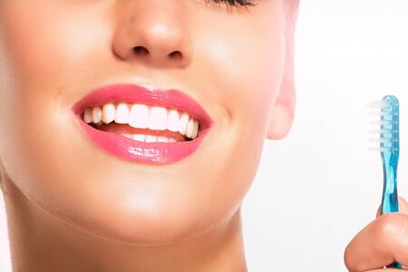 Closeup of smiling woman with perfect white teeth on white photo