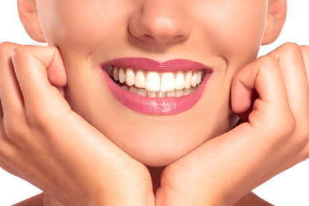 perfect teeth: Closeup of smiling woman with perfect white teeth on white