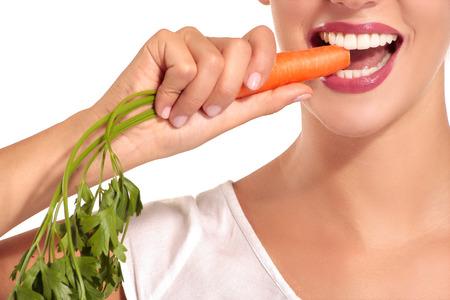 comidas saludables: La hermosa muchacha en una camisa blanca muerde zanahorias en blanco Foto de archivo