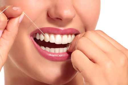 toothcare: Closeup of smiling woman with perfect white teeth on white