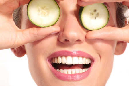 eye mask: Young beautiflul smiling girl applying a cucumber beauty treatment on white