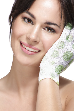Beautiful young woman applying scrub glove on her perfect skin on white photo