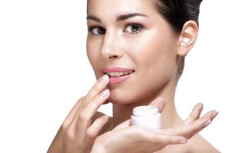Young beautiful woman applying cream treatment on skin white background Standard-Bild