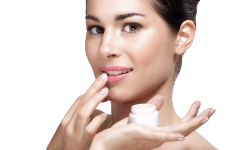 Young beautiful woman applying cream treatment on skin white background Stock Photo