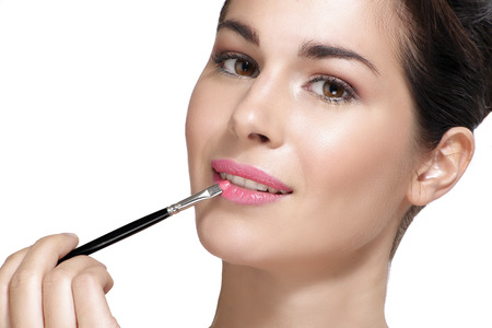 put up: Beautiful young woman applying lipstick with brush on white