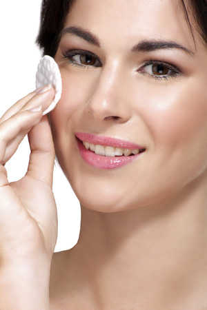 removing make up: young beautiful woman remove makeup from perfect skin on white
