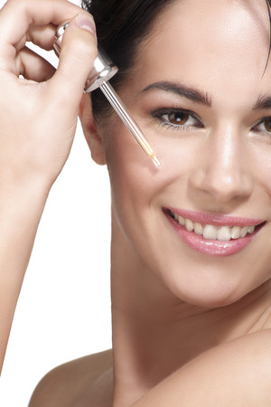 beautiful model applying a skin serum treatment on white Archivio Fotografico