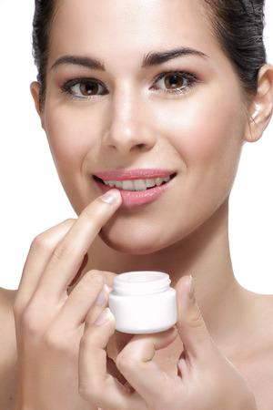 Young beautiful woman applying cream treatment on skin white background Archivio Fotografico