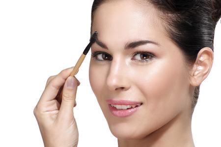 eye brow: Beautiful young woman applying eyebrow brush on white