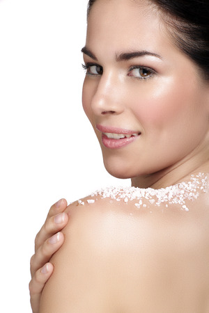 Beautiful young woman applying scrub treatment on the skin  on white Stock Photo