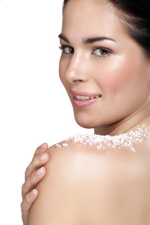 sal: Joven y bella mujer de aplicar el tratamiento exfoliante sobre la piel en blanco