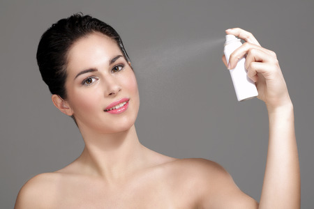 water spray: Beautiful woman applying spray water on face on neutral background