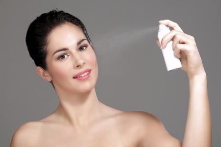 visage: Belle femme appliquant de l'eau de pulv�risation sur le visage sur fond neutre