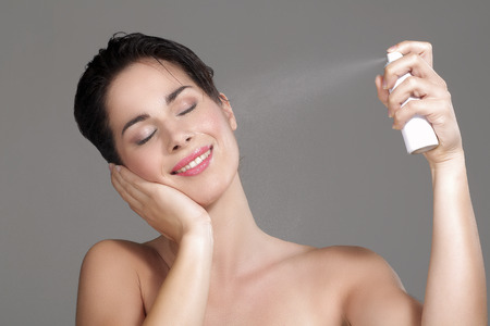 Hermosa mujer de aplicar el spray de agua en la cara en el fondo neutro