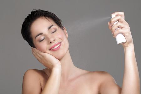 ansikten: Vacker kvinna ansöker sprut vatten i ansiktet på neutral bakgrund