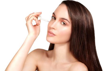 Hermosa modelo de la aplicación de un tratamiento con suero cosmético para la piel en blanco
