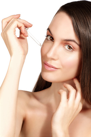 serum: Beautiful model applying a cosmetic skin serum treatment on white