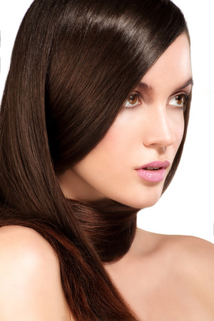 Beauty model showing perfect skin and long healthy brown hair on white Stock Photo