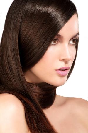 ojos marrones: Modelo de la belleza que muestra la piel perfecta y el pelo largo marr�n saludable en blanco