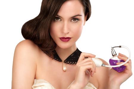 Hermosa mujer perfume apllying mirando en la cámara en blanco Foto de archivo